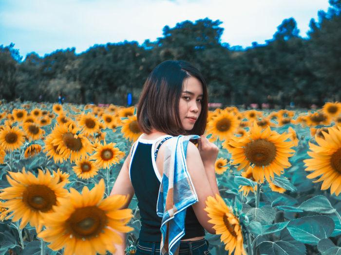 Full length of girl standing on sunflower field