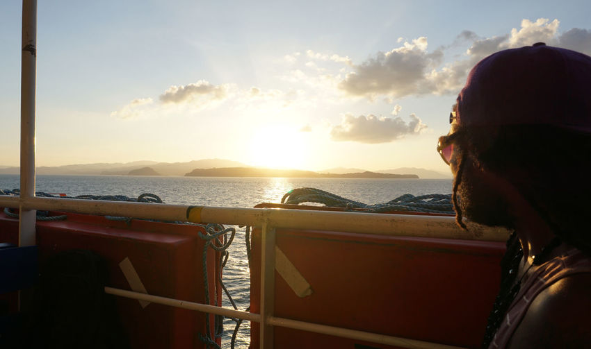Close-up of woman on sea against sky during sunset