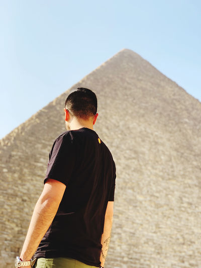 Rear view of man standing against pyramid
