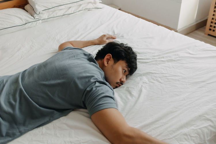 High angle view of man sleeping on bed