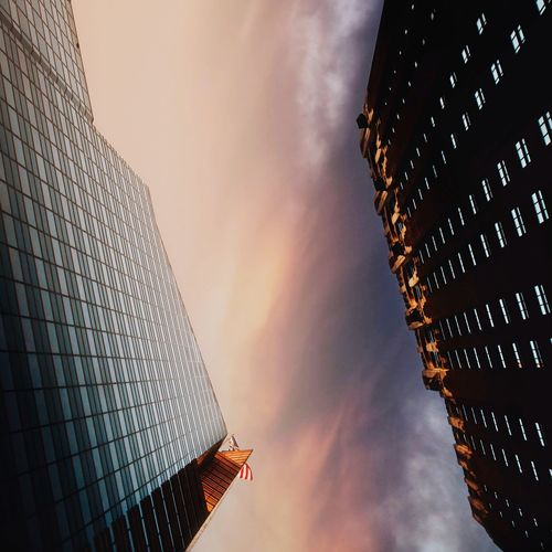 Directly below shot of modern building against sky during sunset