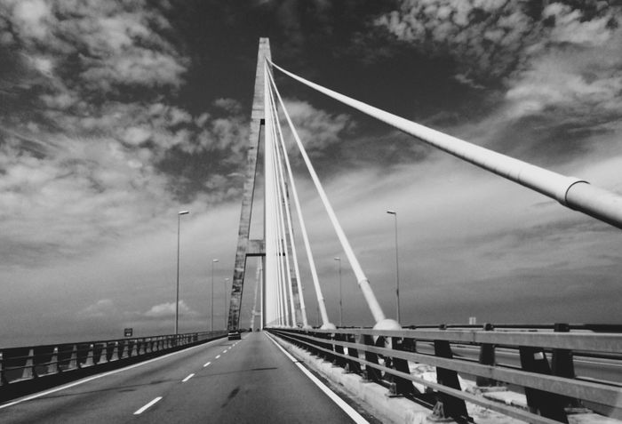 EyeEmNewHere Bridge - Man Made Structure Transportation Connection Road Sky Suspension Bridge Outdoors The Way Forward Diminishing Perspective Cloud - Sky Highway Bridge Day Architecture No People Car Built Structure Tree Water Nature
