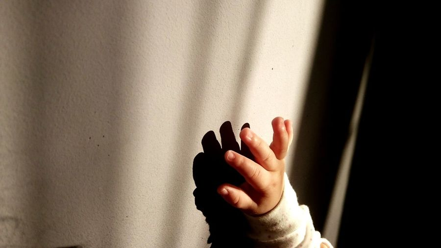 Cropped hand of baby girl by wall with shadow