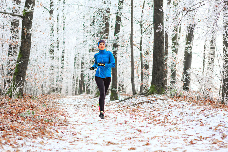 Portrait of woman jogging in forest during winter