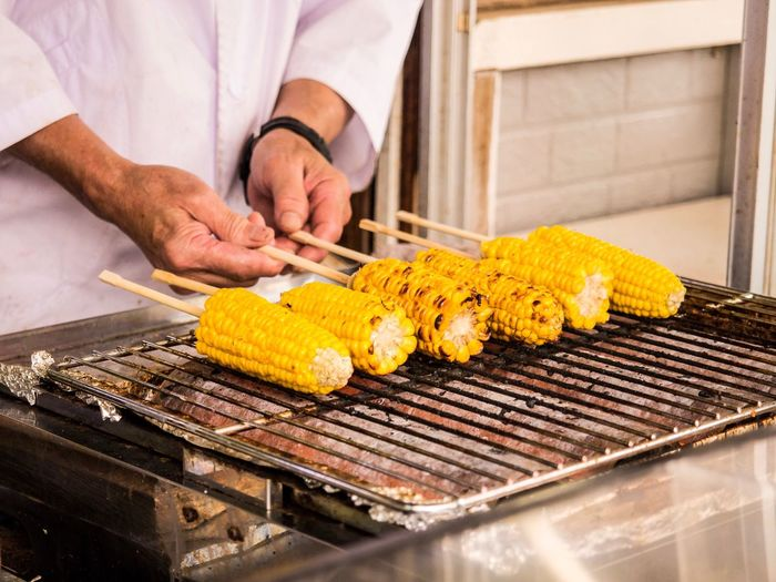 Midsection Of Man Cooking Sweetcorns On Barbecue Grill