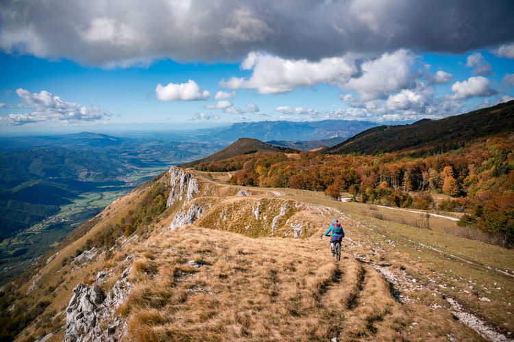 Woman mountain biking on footpath near ridge on mount nanos above vipava, slovenia.