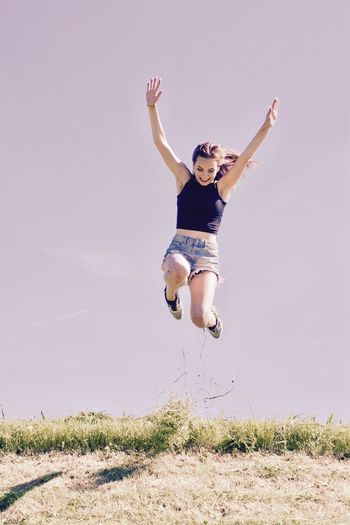 Activity Adult Athlete Cheerful Day Exercising Front View Full Length Grass Happiness Human Body Part Jumping Lifestyles Mid-air Motion Nature One Person One Woman Only Outdoors People Portrait Sky Sport Sports Clothing Vitality