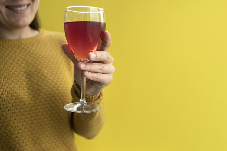 Woman holding wineglass against yellow background