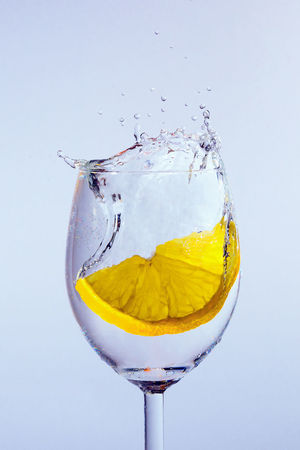 The olive falls into the glass with vodka. Bubbles and splashes appear. Blue background. Freshness Lemonade Alcohol Close-up Coctail Day Drink Drinking Drop Food And Drink Freshness Glass Lemon No People Splashing Studio Shot Water