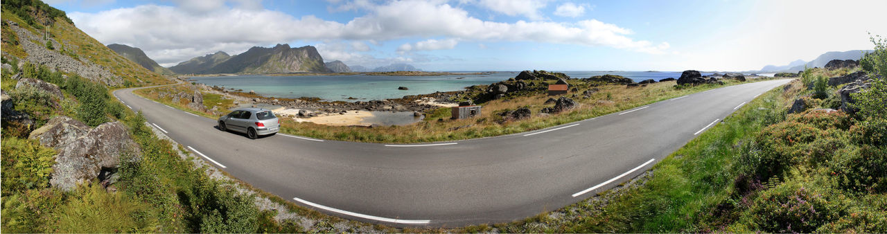 Panorama of a road with a silver car along the coast of Vestvagoy, Lofoten, Nordland, Norway Adventure Atlantic Road Bay Beach Boathouse Car Coastal Coastline Drive Fjord Island Landscape Lofoten Lonely Mountain Range Panoramic Panoramic View Red House Roadtrip Rolvsfjorden Round Trip Sea Valberg Valbergsveien Vestvågøy