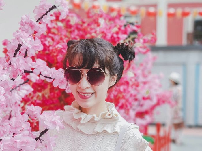 Portrait Of Smiling Woman In Sunglasses By Pink Flowers