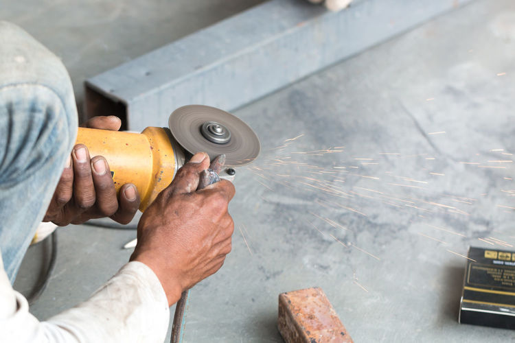 Hands of Worker using angle grinder tool to cutting steel bar with fire sparking. Construction Construction Site Cutting Machine Man Work Worker Working Workplace Angle Grinder Blade Cement Circular Concrete Dust Electricity  Equipment Floor Human Body Part Human Hand Indrustrial Outdoors People Saw Tool