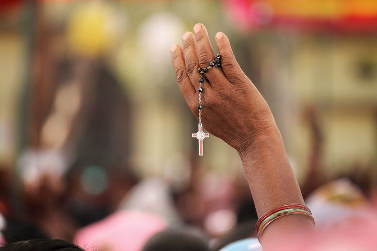 Close-up of woman holding rosary in hand against blurred background