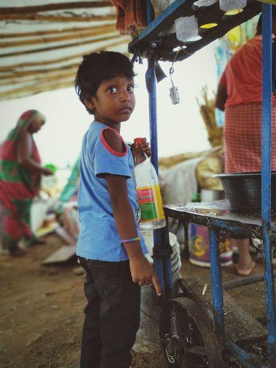 Side view of boy holding bottle in village