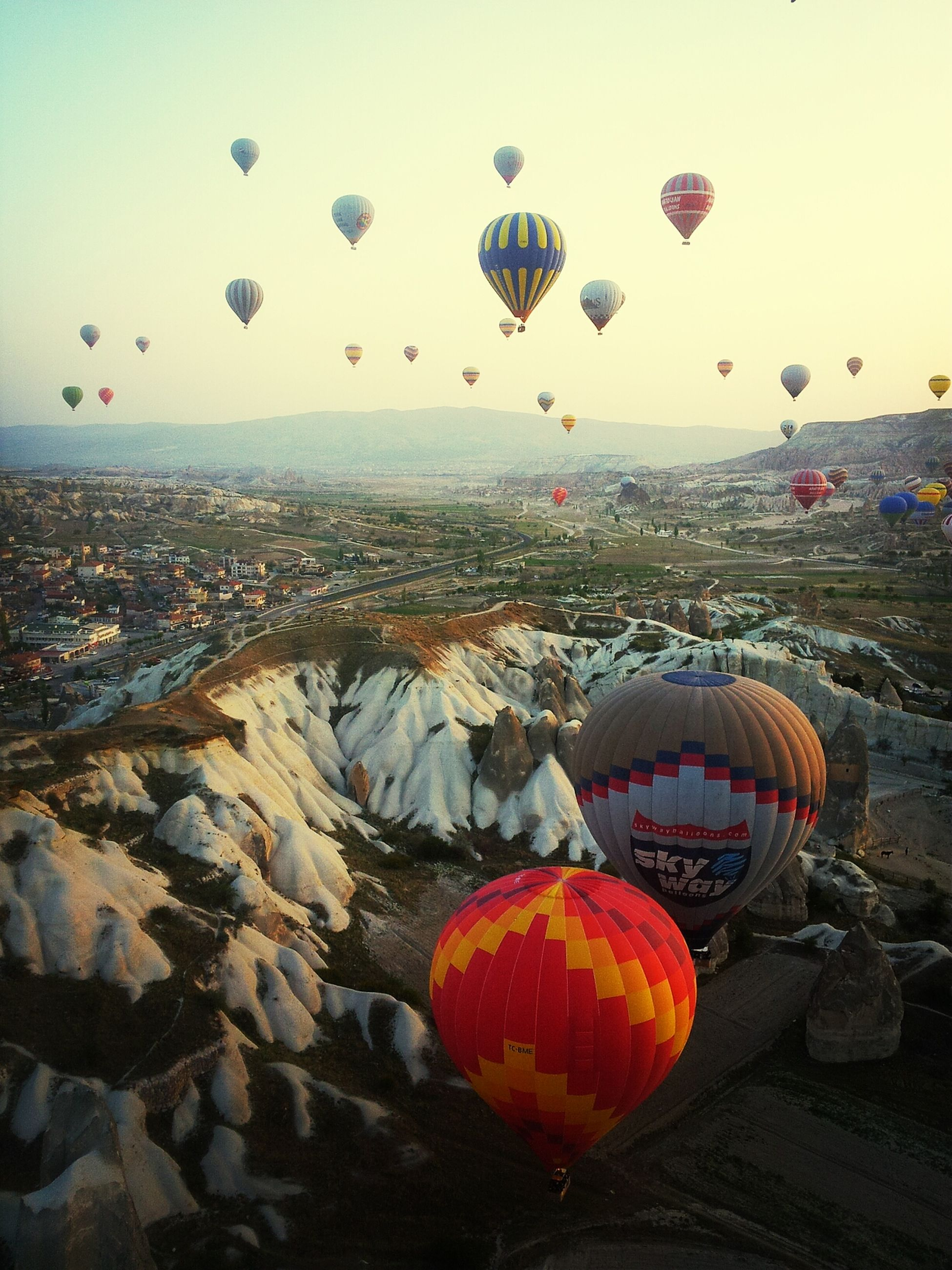 sky, hot air balloon, mid-air, multi colored, sunset, flying, transportation, outdoors, balloon, sea, celebration, scenics, no people, clear sky, nature, sun, tranquility, dusk, tradition, orange color