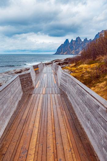 Empty boardwalk by sea against cloudy sky