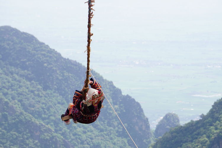 Rear view of woman on akha swing against mountain