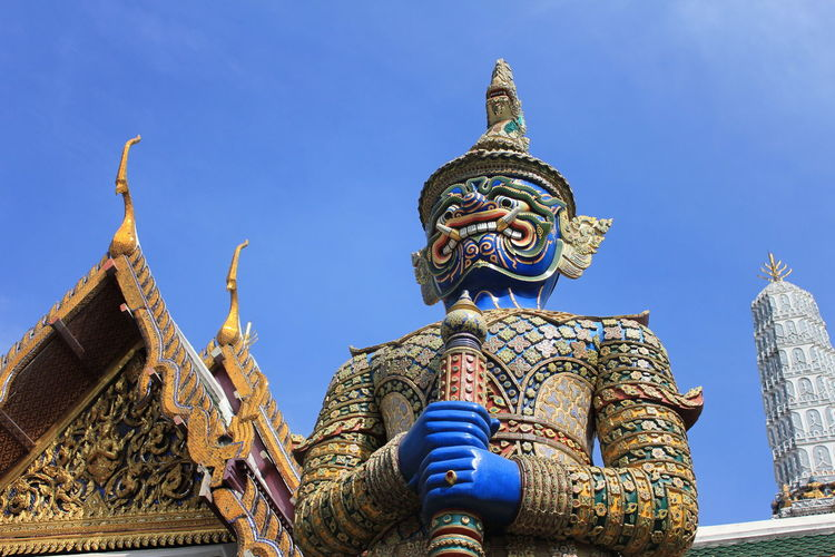 Low angle view of monster statue and temple against blue sky