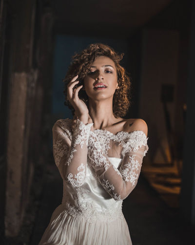 Portrait Of Sensuous Woman In Wedding Dress Standing At Home