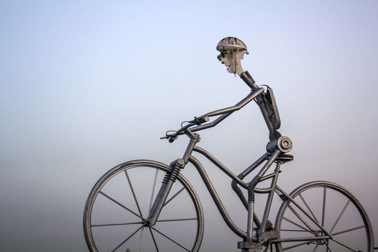 Metal man with giant bicycle. Sport and active life concept Biking Exercise Healthy Habits Sustainable Transport Active Life Athelete Awareness Bicycle Bike Clear Sky Concept Copy Space Cycling Day Fitness Healthy Mode Of Transportation No People Outdoors Sky Sport Transportation