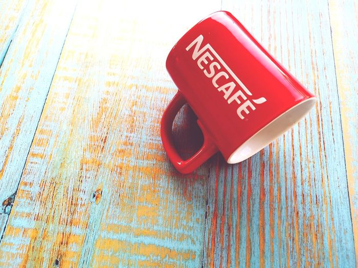 Nescafe mug over blue wooden background with selective focus. Attractions❤️ Selective Focus Object Nescafe Mug Red Color Colors Color Mug Nescafe Red Text Wood - Material Close-up Information
