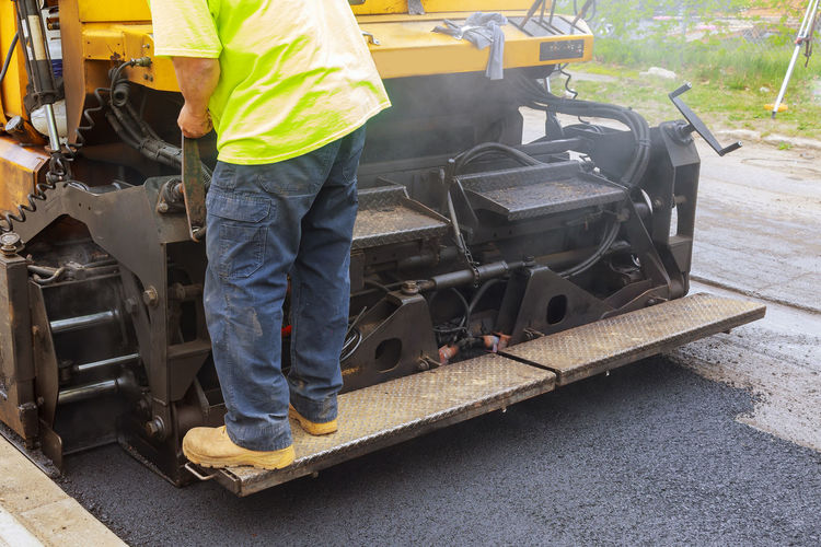 Low section of man operating construction machinery on road
