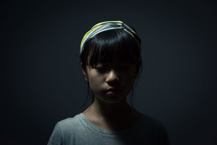 Close-Up Of Girl Against Black Background