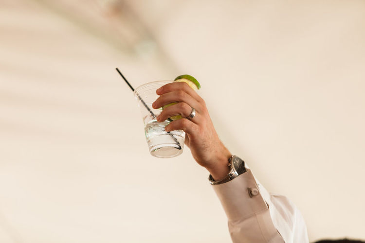 Cropped hand of man holding drink against wall