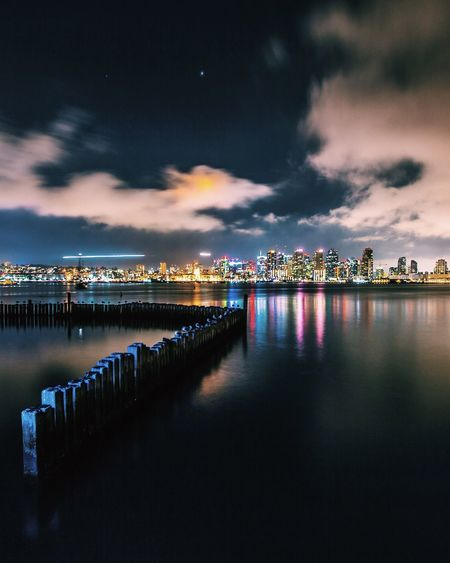 Groyne In River By Illuminated City At Night