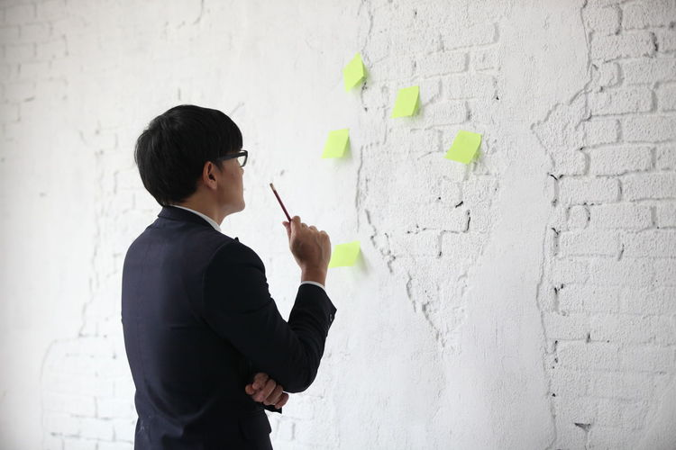 Side view of boy standing against white wall