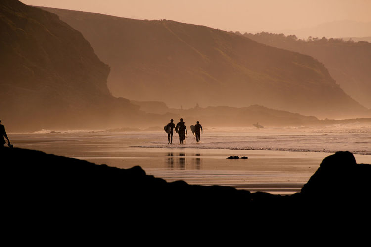 Silhouette Surfers On Beach