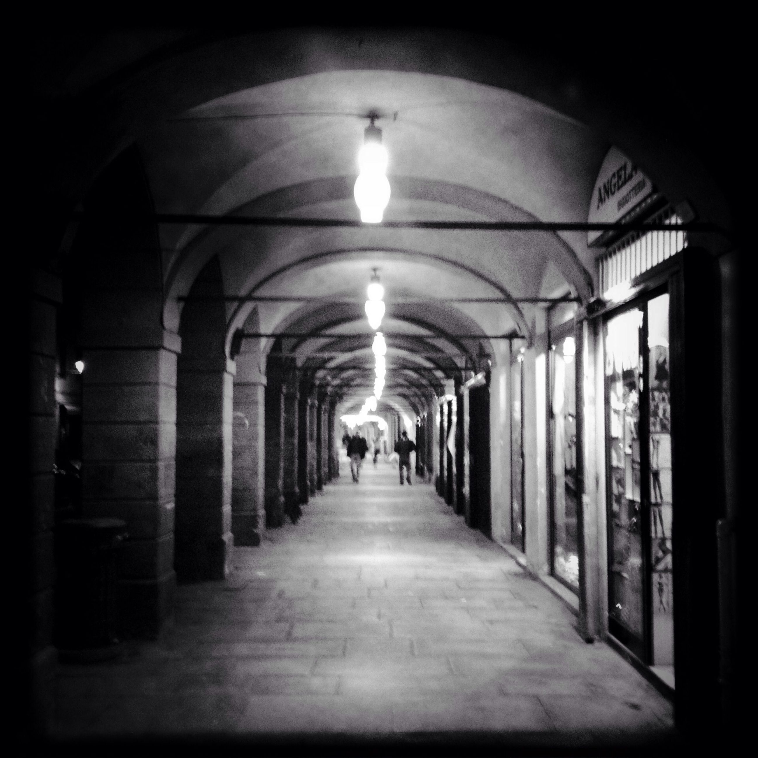 indoors, arch, the way forward, architecture, corridor, built structure, illuminated, ceiling, diminishing perspective, lighting equipment, in a row, archway, tunnel, architectural column, vanishing point, incidental people, colonnade, empty, walkway, flooring