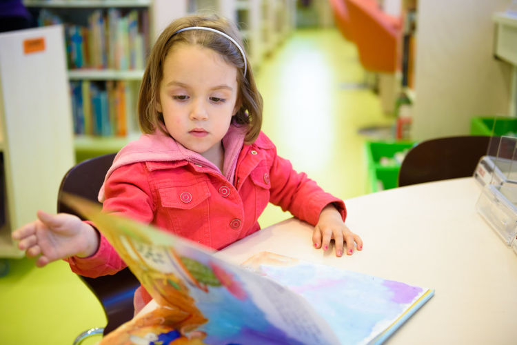 Girl reading book while sitting on chair in library