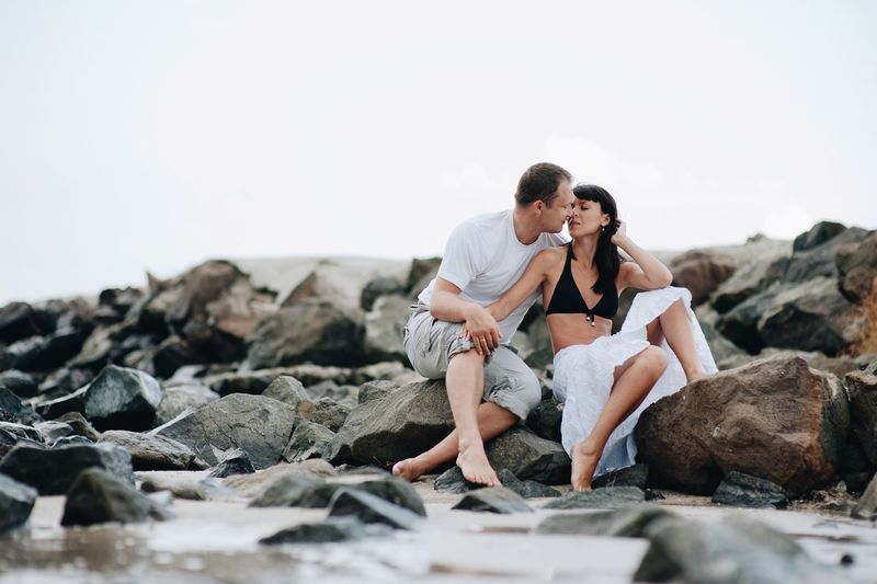 Couple kissing at beach against sky