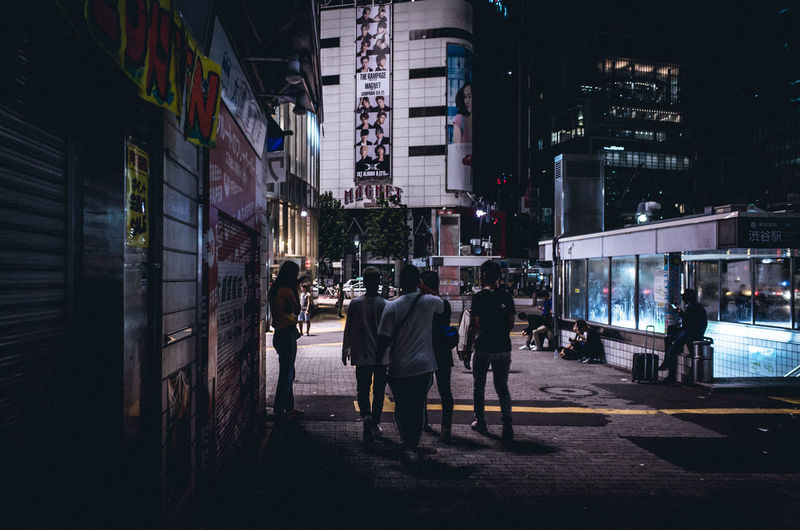 People walking on street at night in city