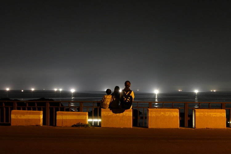 Rear view of family sitting on seat against sea at night