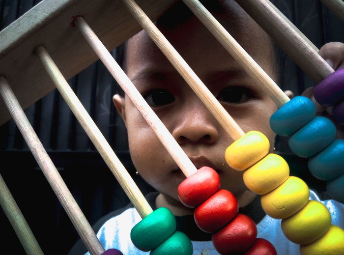 Close-up portrait of cute baby girl looking through abacus