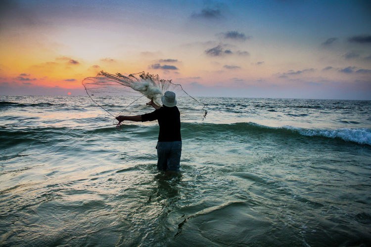 Rear view of man throwing fishing net in sea during sunset
