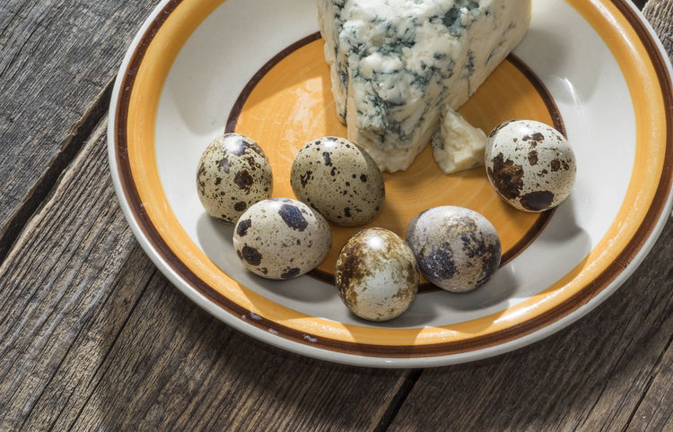 Quail eggs and roquefort cheese on a plate on an old wooden weathered table Wooden Quail Eggs Weathered Blue Bowl Cheese Close-up Day Food Food And Drink Freshness Healthy Eating High Angle View Indoors  No People Old Old Buildings Plate Ready-to-eat Roquefort Table Wood - Material