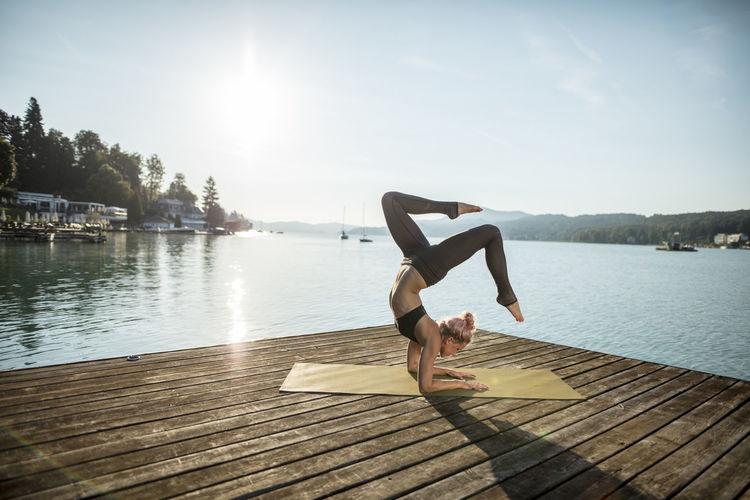 Full length of man relaxing on pier over lake against sky