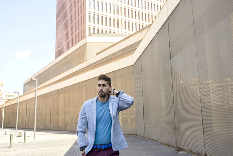 Full length of young man standing against modern building