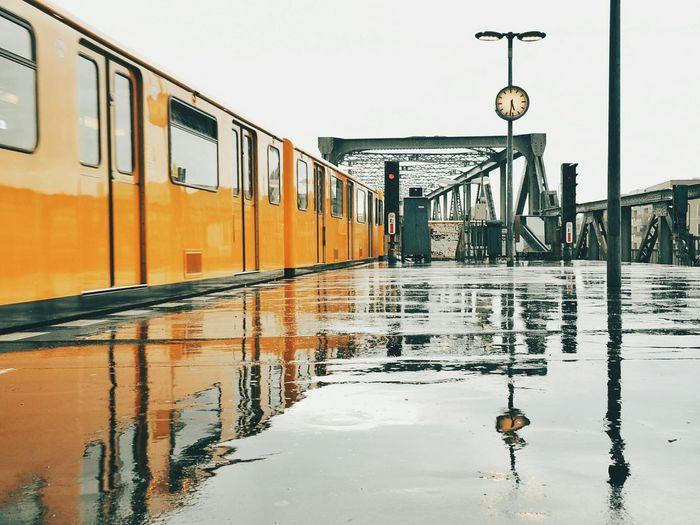 Reflection Of Train And Clock On Wet Railroad Station Platform During Monsoon