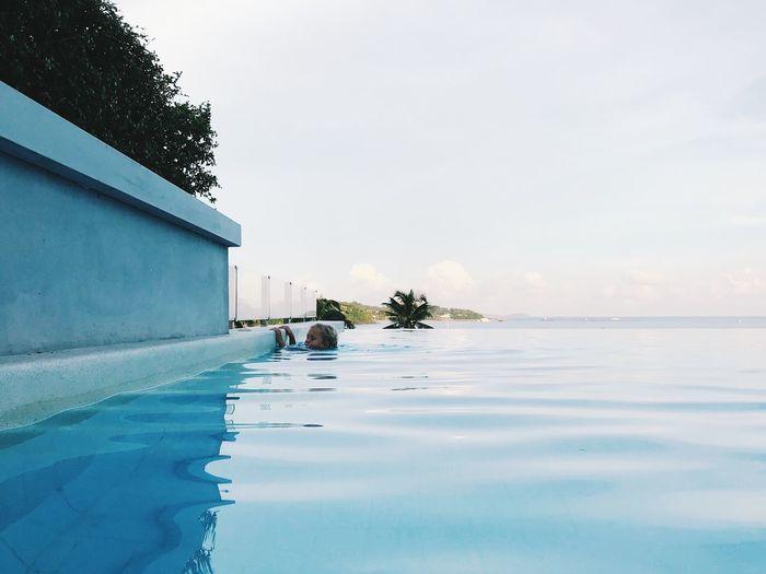 Girl swimming in pool against sky