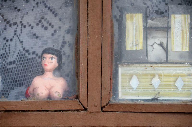 Portrait of shirtless man lying on window sill