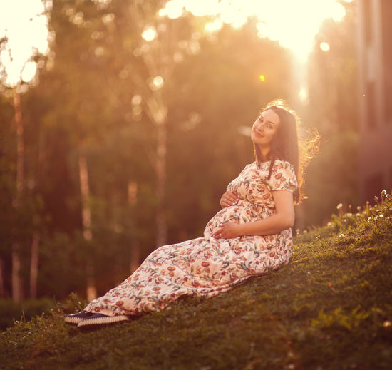 Portrait of pregnant woman touching abdomen while sitting on grass