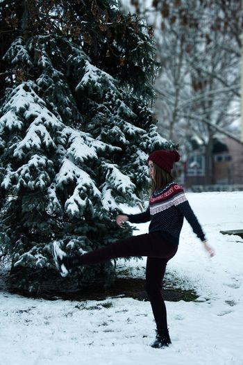 Full length of woman kicking snow by tree