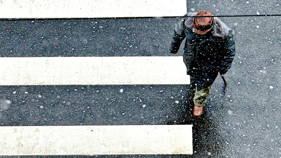 High Angle View Of Man Crossing Road In City During Snowfall