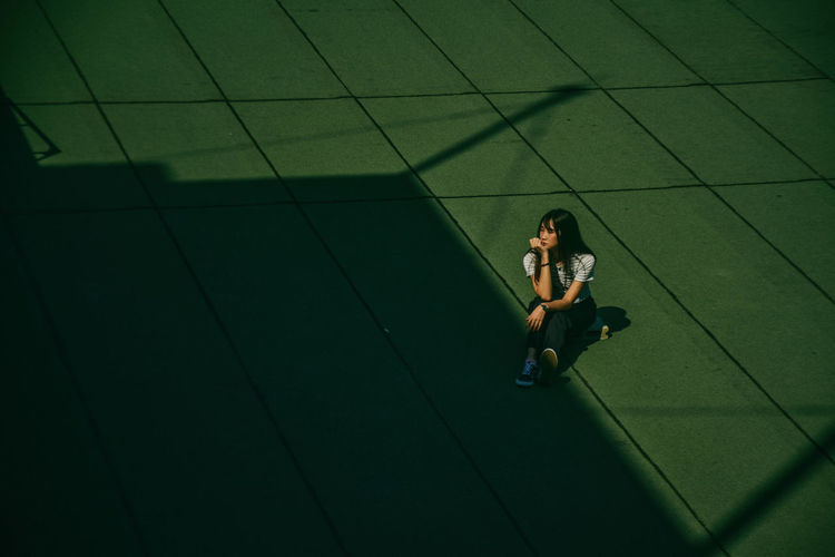 High angle view of woman sitting on floor