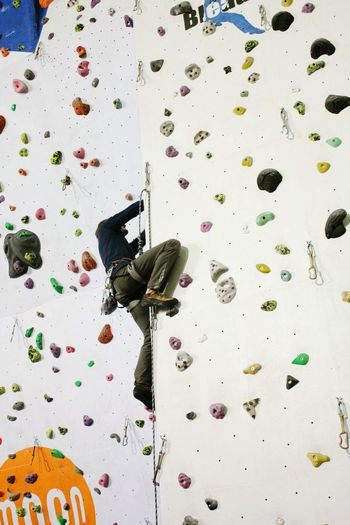 Low Angle View Of Man Climbing Artificial Wall