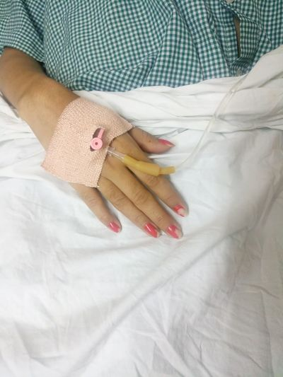 Midsection of female patient with iv drip in hospital